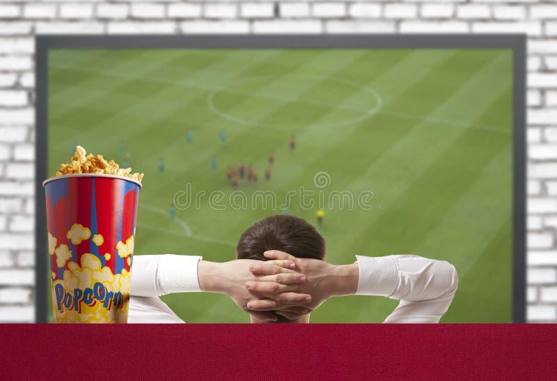 Jogo de futebol de observação na tevê imagens de stock