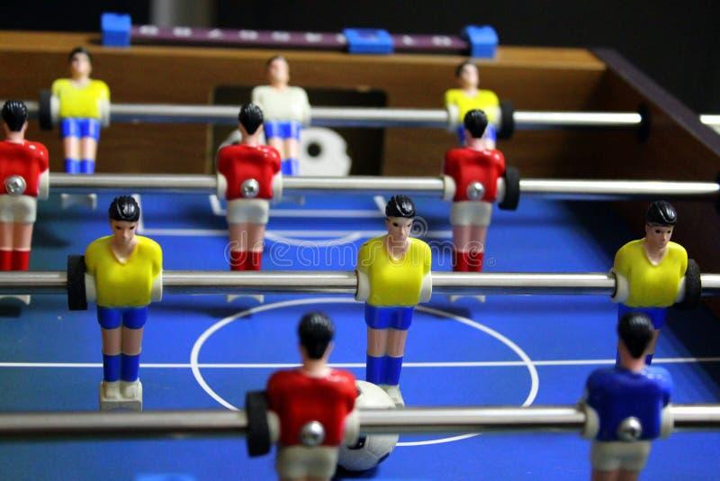 Jogo de futebol do futebol da tabela retrocesso jogadores de equipe dos esportes em t-shirt vermelhos e amarelos foto de stock royalty free