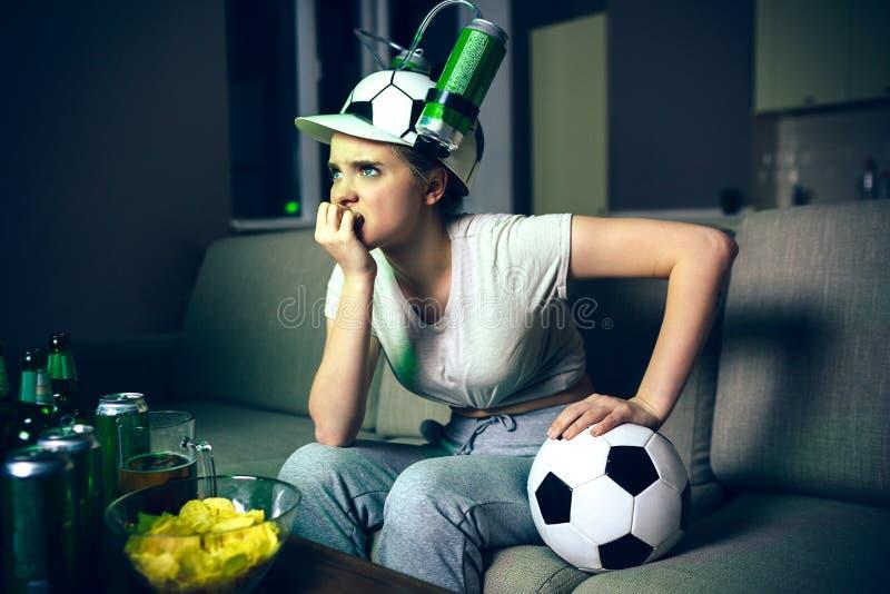 Jogo de futebol do relógio da jovem mulher na tevê na noite Modelo virado irritado que inclina-se para a frente Mão da posse na b imagem de stock royalty free