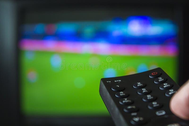 Jogo de futebol e televisão de observação guardar de controle remoto foto de stock