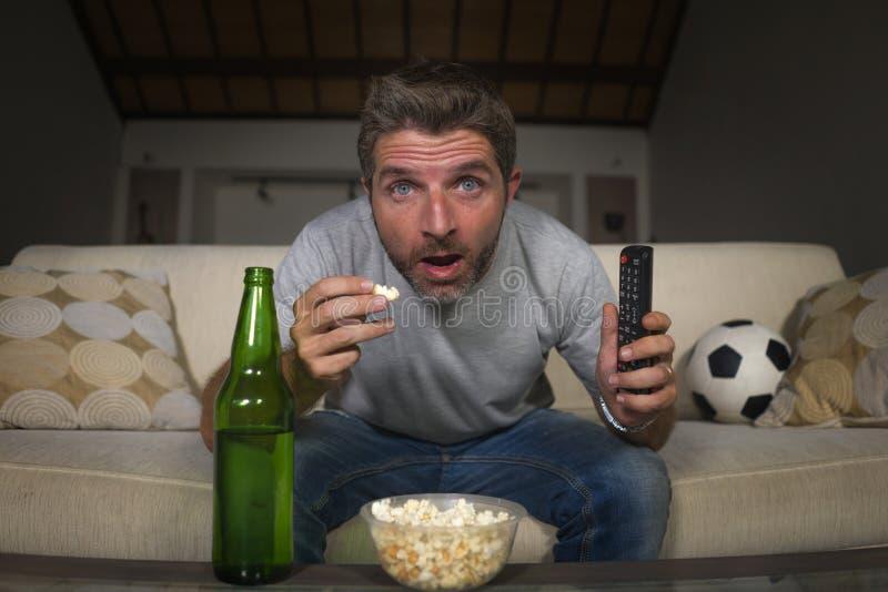 Jogo de futebol de observação atrativo do homem nervoso e entusiasmado do suporte do futebol no sofá do sofá da televisão em casa fotos de stock royalty free