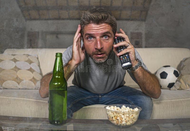 Jogo de futebol de observação atrativo do homem nervoso e entusiasmado do suporte do futebol no sofá do sofá da televisão em casa imagem de stock