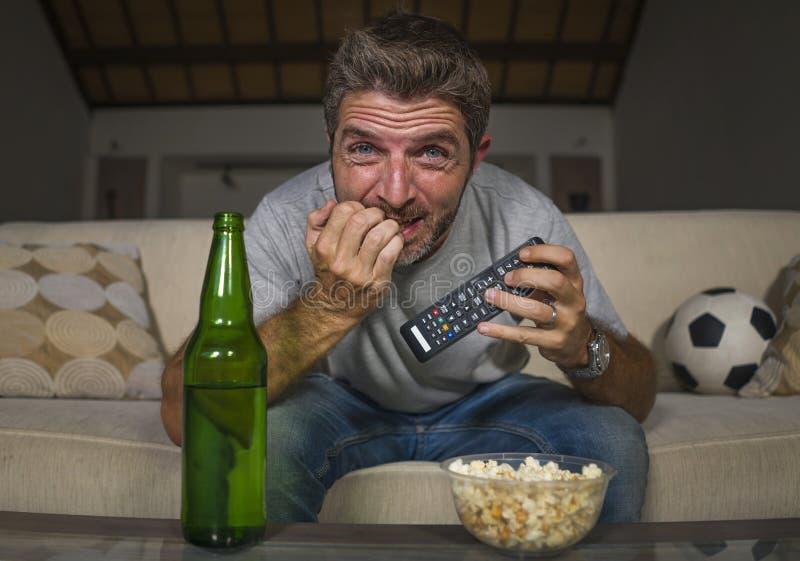Jogo de futebol de observação do homem entusiasmado do suporte do futebol no sofá do sofá da televisão em casa no esforço e na em imagens de stock