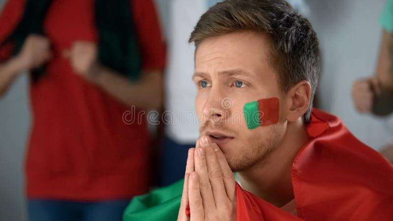 Jogo de futebol de observação do suporte de Portugal na tevê, rezando para a vitória, close up foto de stock royalty free