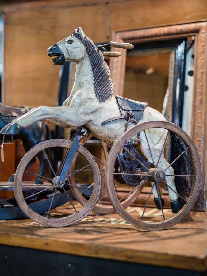 Jogo de madeira antigo: Cavalo de balanço com três rodas fotografia de stock royalty free