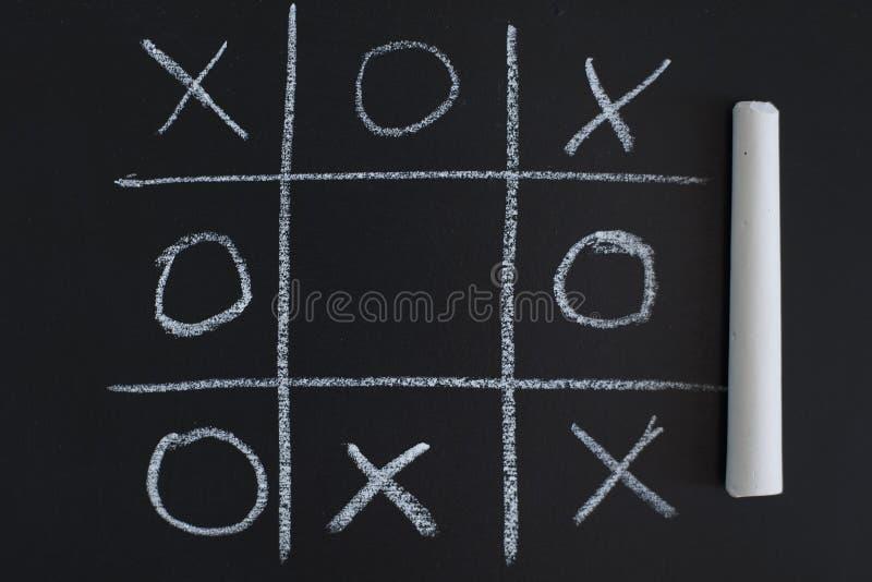 Jogo de O X na placa de giz preta imagem de stock royalty free