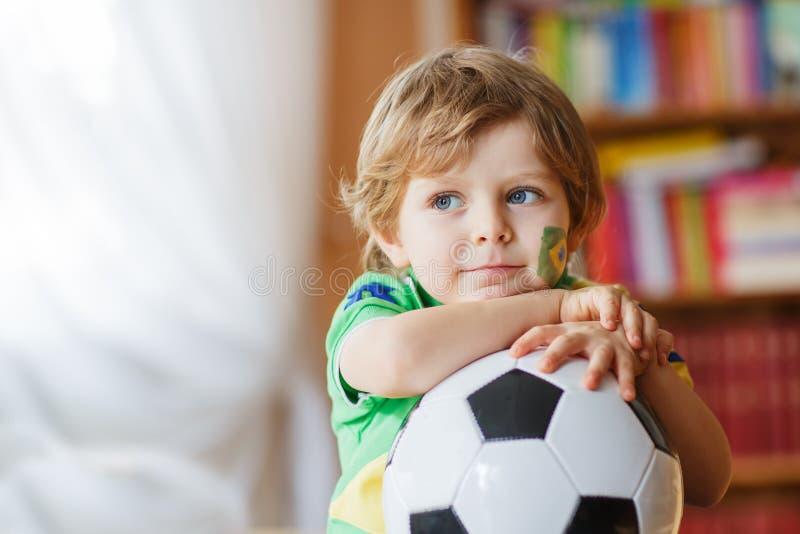Jogo de observação do copo do futebol do rapaz pequeno na tevê fotografia de stock royalty free