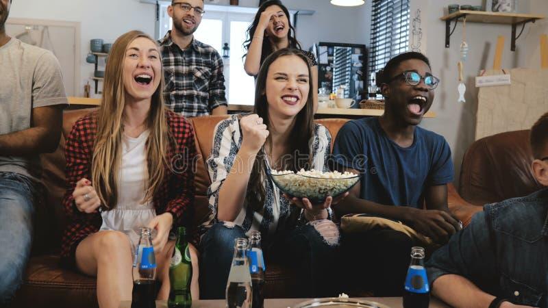 Jogo de observação dos esportes do grupo misturado da afiliação étnica na tevê Fãs emocionais no sofá com bebidas e fim do movime fotos de stock
