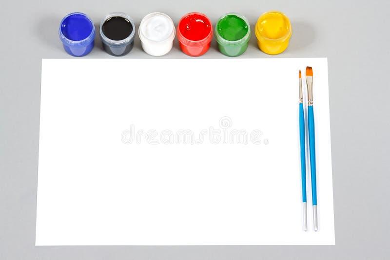 Jogo de pinturas do gouache da arte e escovas e papel fotos de stock