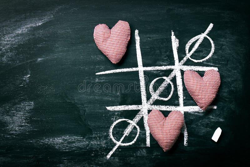 Jogo de Tac Toe do tique Conceito do dia do ` s do amor ou do Valentim com Chalkboar fotos de stock