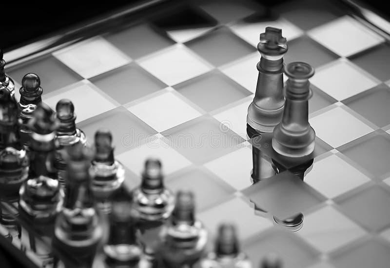 Jogo de xadrez de vidro, rei com partes de xadrez BW da rainha fotografia de stock