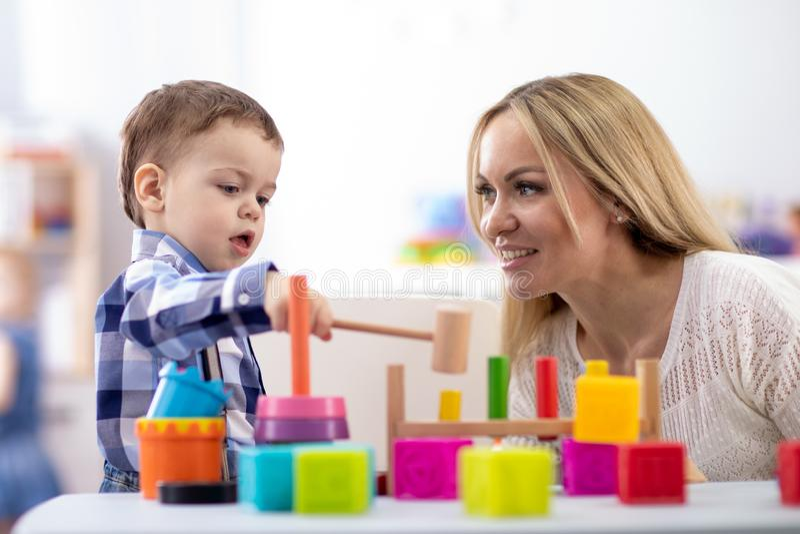 Jogo do beb? e do cuidador do ber??rio com os brinquedos do montessori na tabela no centro de guarda foto de stock