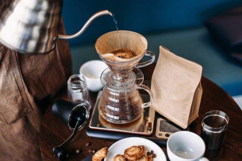Jogo do café do gotejamento da mão, água de derramamento do barista na sagacidade da borra de café fotografia de stock royalty free