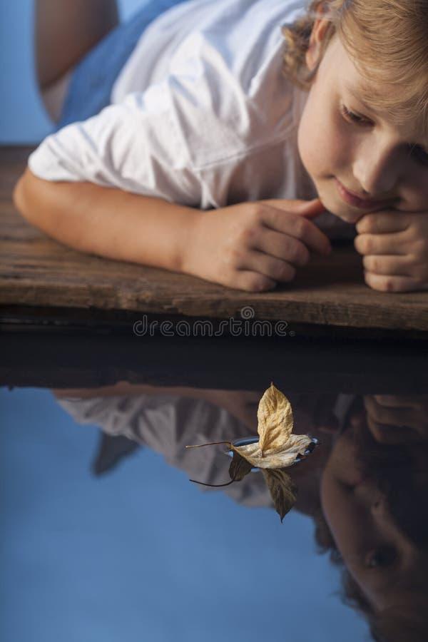 Jogo do menino com o navio da folha na água imagem de stock royalty free