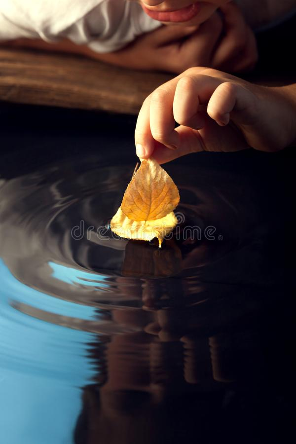 Jogo do menino com o navio da folha na água foto de stock royalty free