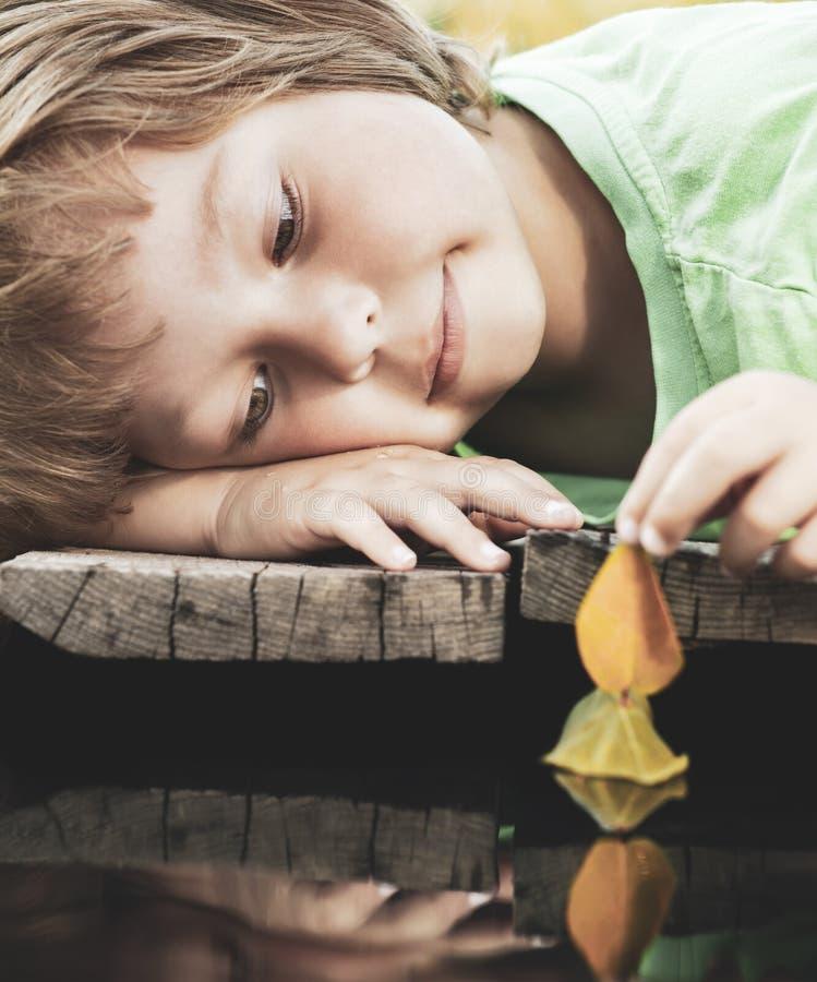 Jogo do menino com o navio da folha do outono na água, crianças no jogo do parque com a folha no rio imagem de stock