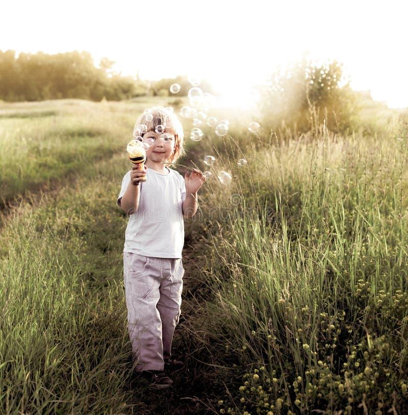 Jogo do menino nas bolhas fotos de stock