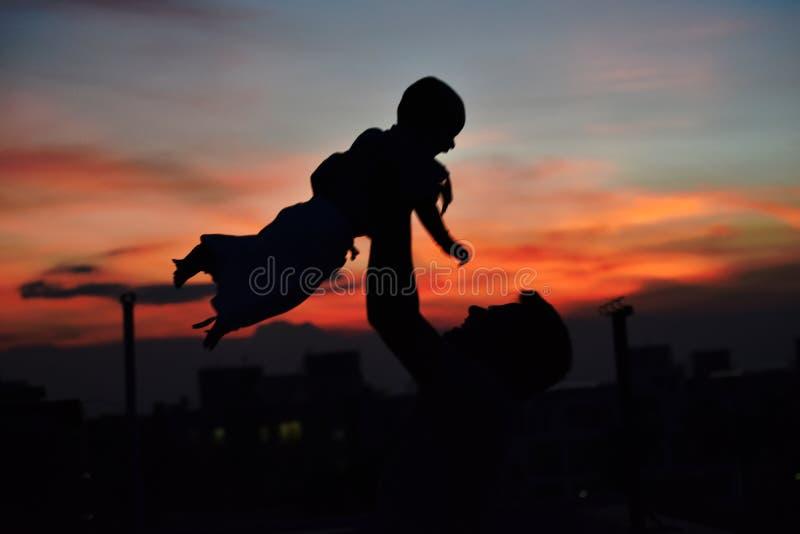 Jogo do pai e da filha durante o por do sol imagens de stock