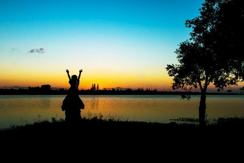 Jogo do pai seu filho no por do sol do rio imagens de stock