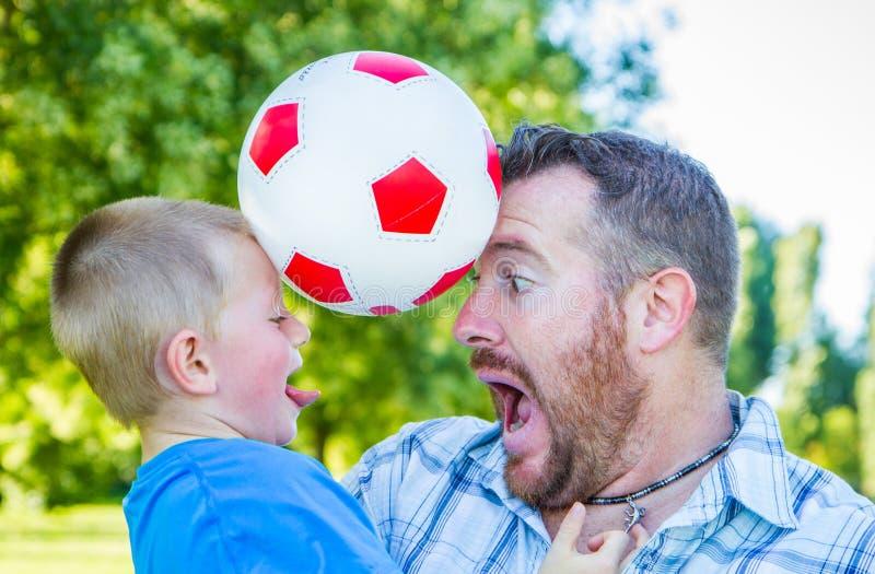 Jogo do paizinho e do rapaz pequeno com a bola imagem de stock