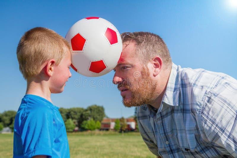 Jogo do paizinho e do rapaz pequeno com a bola fotos de stock royalty free