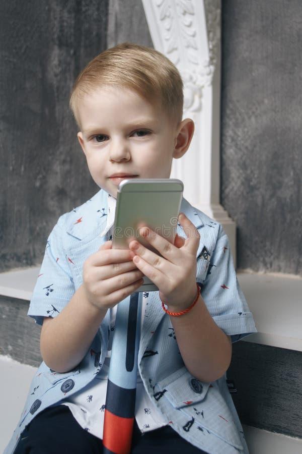 Jogo do rapaz pequeno com smartphone foto de stock royalty free