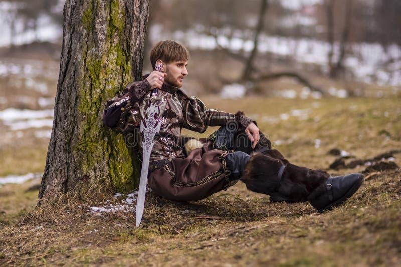 Jogo do traje Cavaleiro caucasiano com a espada que senta-se perto da árvore contra o fundo do rio da natureza fotos de stock