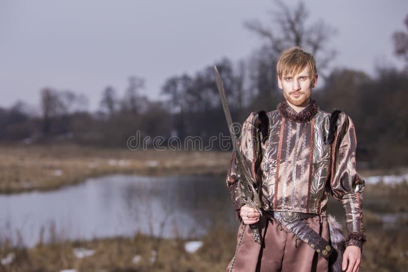 Jogo do traje Espada do wirh do guerreiro que levanta na roupa medieval contra o ar livre do rio foto de stock royalty free