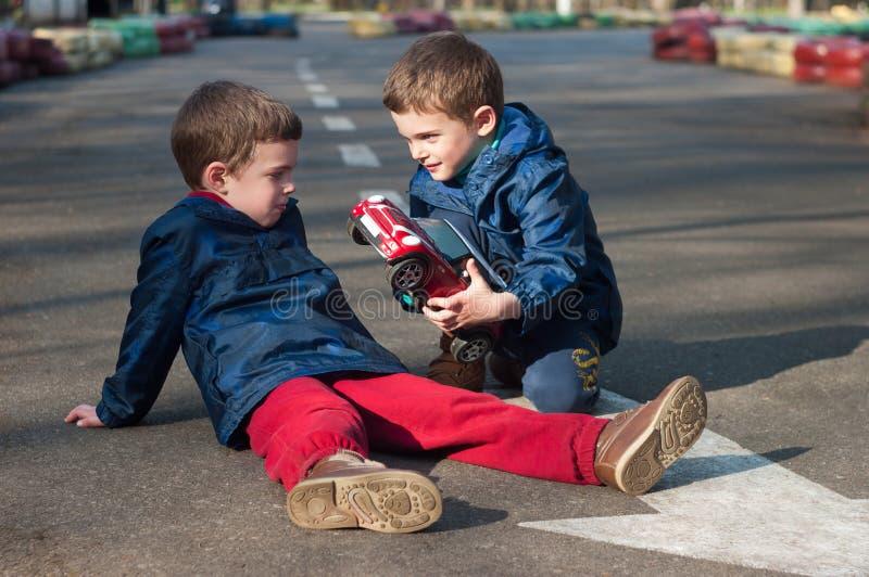 Jogo dos irmãos gêmeos com um carro do brinquedo imagem de stock