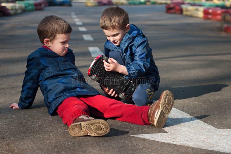Jogo dos irmãos gêmeos com um carro do brinquedo fotografia de stock