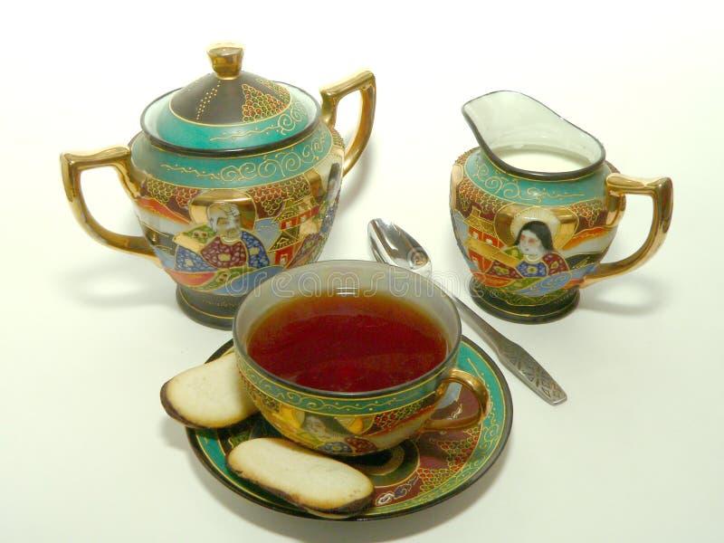 Jogo e biscoitos de chá oriental no fundo isolado imagem de stock