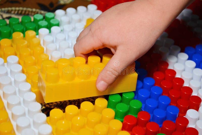 Jogo e descoberta do bebê com brinquedos coloridos em casa, detalhe do close-up Brincadeiras com blocos de apartamentos plásticos fotos de stock royalty free
