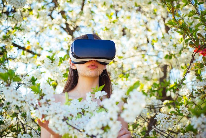 Jogo e entretenimento Simulação virtual da tecnologia Vidros do vr do desgaste da jovem senhora na flor da mola Jogo bonito da me fotografia de stock