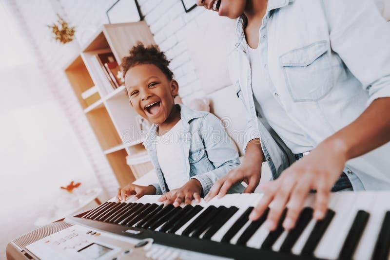 Jogo feliz da mãe do amd engraçado da menina no piano junto imagem de stock