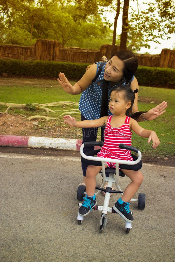 Jogo feliz da mam? com sua crian?a ao empurrar um carrinho de crian?a no parque imagens de stock