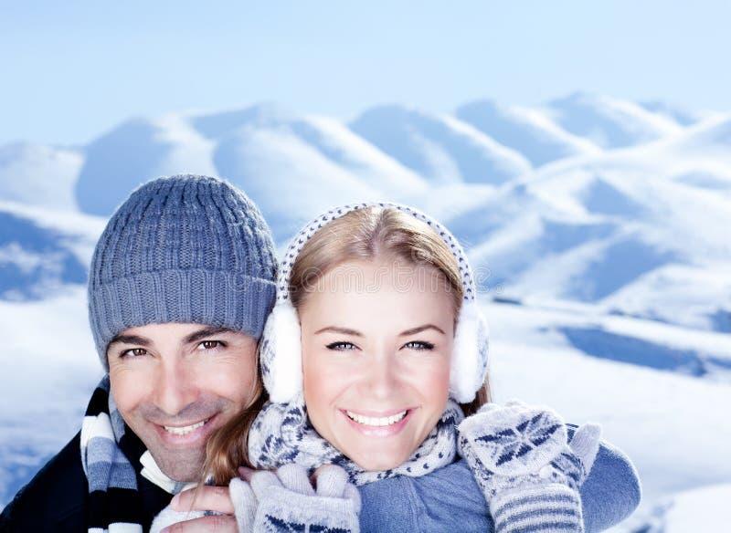 Jogo feliz dos pares ao ar livre em montanhas do inverno fotografia de stock
