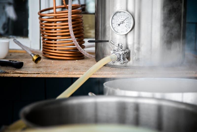 Jogo home da fabricação de cerveja e Wort de derramamento da cerveja do ofício na fervura Kettl imagem de stock