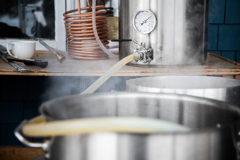 Jogo home da fabricação de cerveja e Wort de derramamento da cerveja do ofício na fervura Kettl imagem de stock royalty free