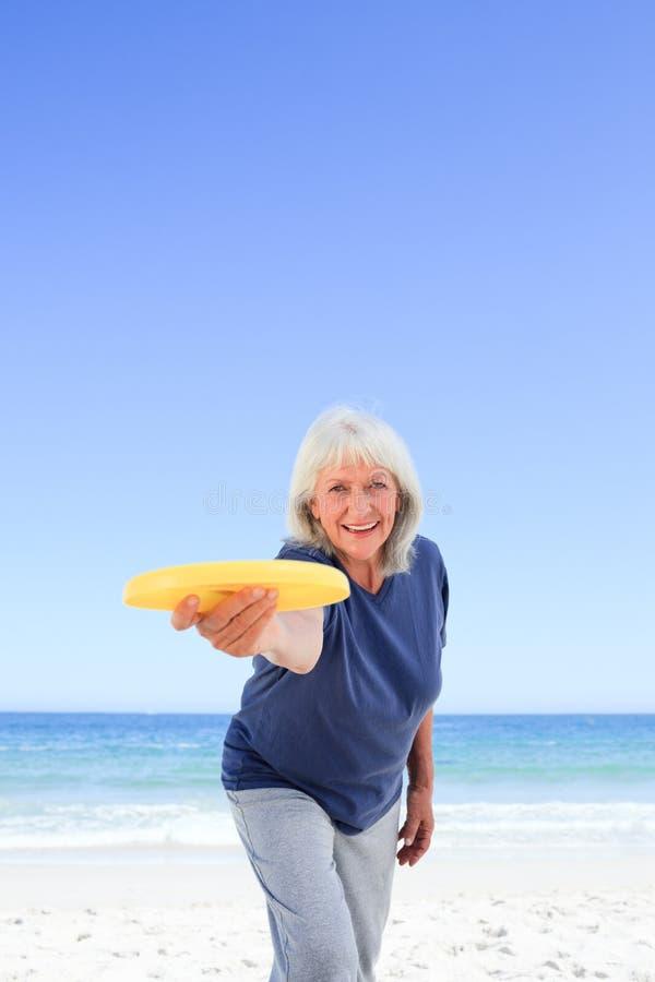 Jogo idoso da mulher freesby fotos de stock