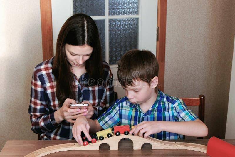 Jogo junto A mamã olha o telefone e o filho está jogando uma estrada de ferro de madeira com o trem, os vagões e o túnel sentando fotos de stock royalty free