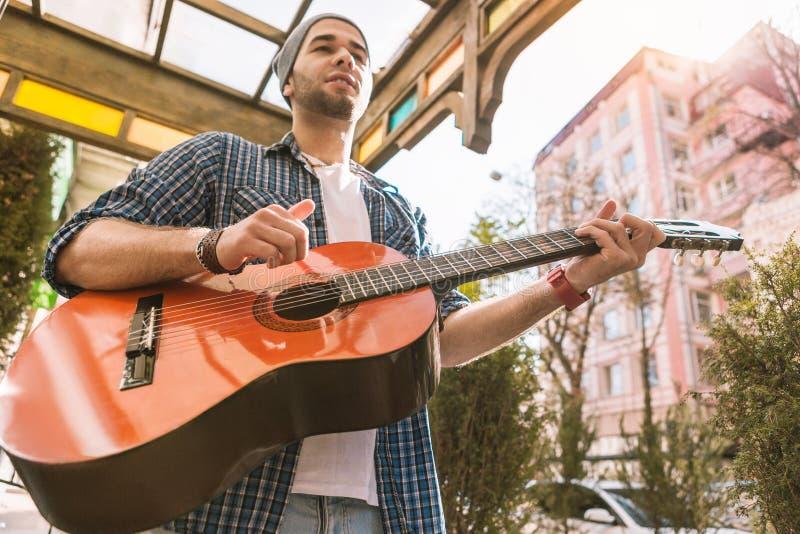 Jogo masculino pensativo do treinamento do guitarrista na rua imagens de stock royalty free