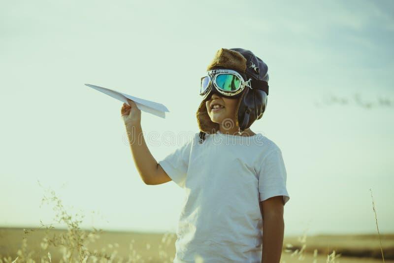 Jogo, menino que joga para ser piloto do avião, indivíduo engraçado com aviador c imagem de stock