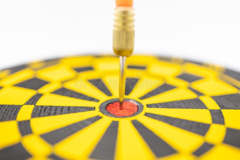 Jogo, negócio, planeamento e conceito do alvo Feche acima da facada do dardo no centro da placa preta e amarela no fundo branco imagem de stock