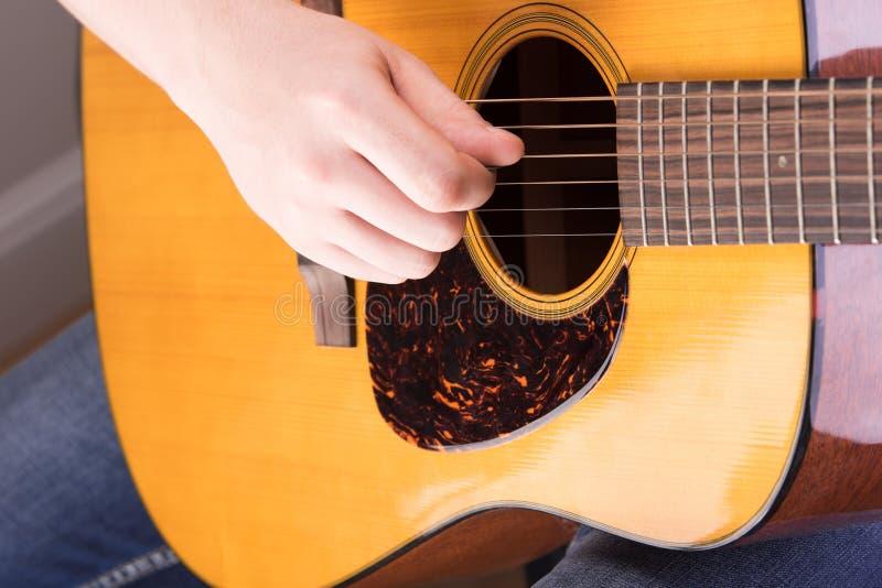Jogo no close-up da guitarra acústica Mão masculina para arrancar o stri fotografia de stock