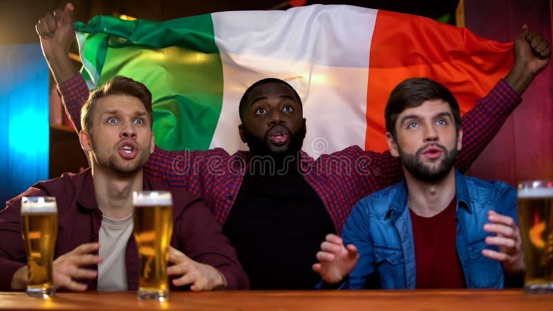 Jogo perdedor italiano da equipe de futebol, amigos masculinos multirraciais decepcionados, bar imagem de stock