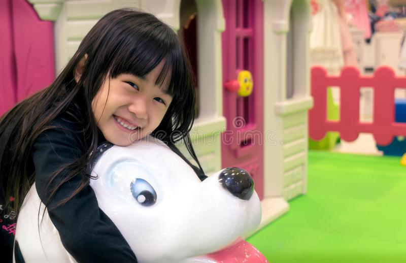Jogos asiáticos da menina em um campo de jogos interno fotos de stock royalty free