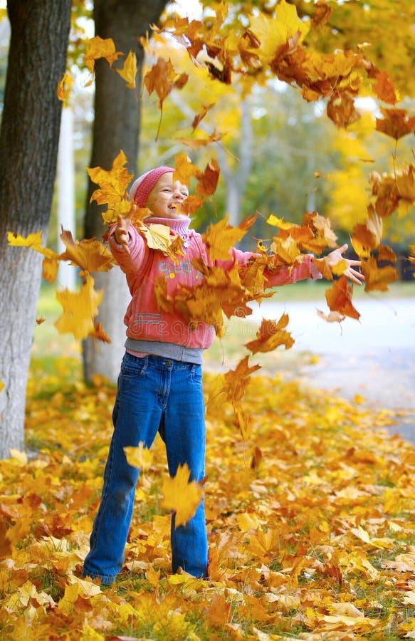 Jogos bonitos da menina com folhas de outono fotos de stock royalty free