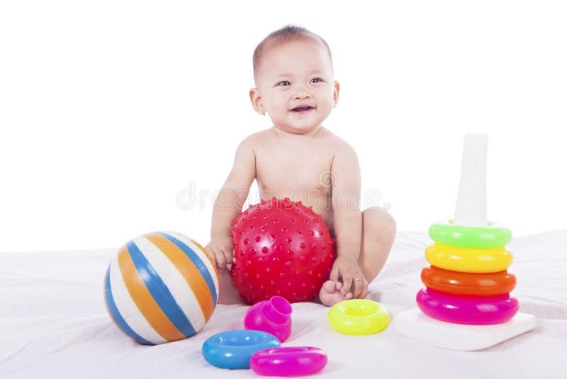 Jogos bonitos do bebê com brinquedos coloridos imagem de stock