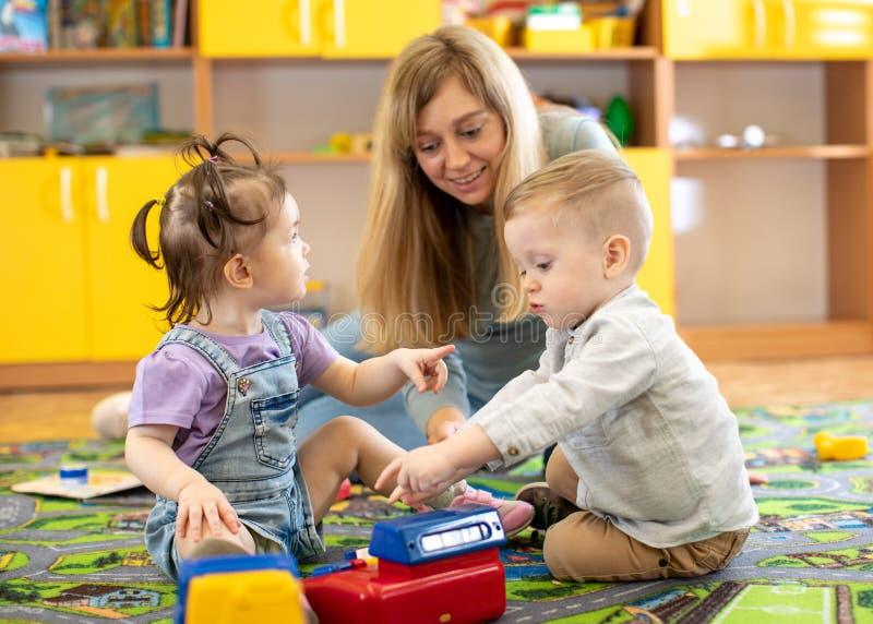 Jogos da baby-sitter com os bebês no berçário imagem de stock