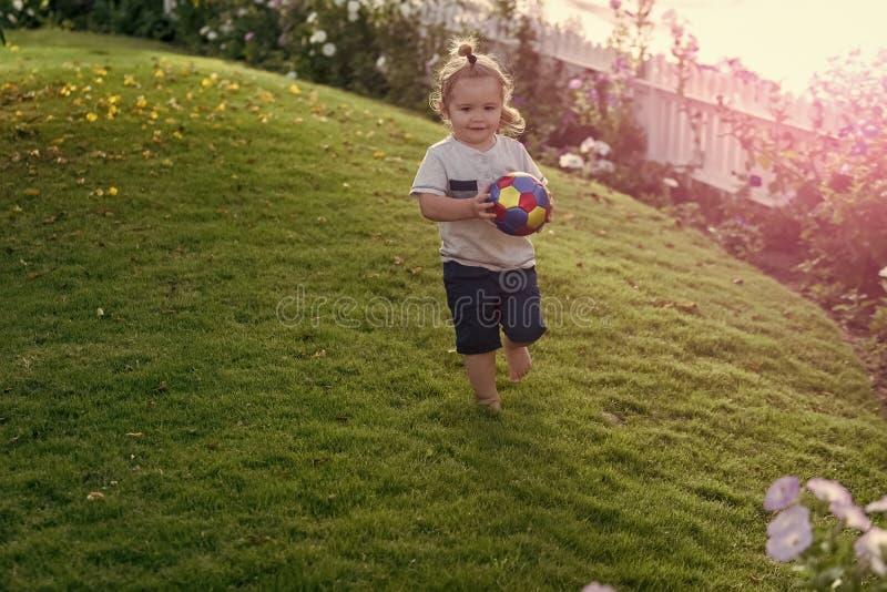 Jogos da criança com bola Energia da infância, atividade, bem-estar imagens de stock royalty free